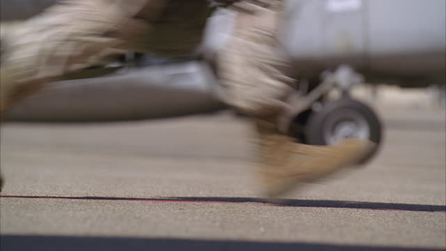 soldiers run across the tarmac at a military base. - boot stock videos & royalty-free footage