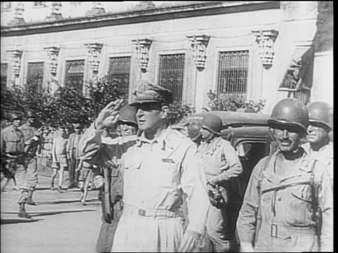Soldiers run outside Santo Tomas prison / General Douglas MacArthur arrives and visits freed civilian prisoners in Manila / crowd cheers and watches...