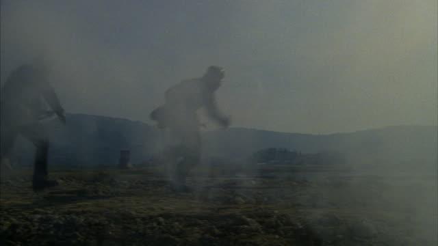 soldiers run through a battlefield during word war ii. - zweiter weltkrieg stock-videos und b-roll-filmmaterial