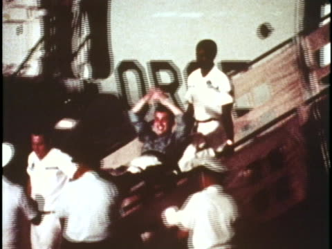 soldiers run to waiting families, as others are carried off a plane on stretchers, during the 1973 vietnam war homecomings. - ホームカミング点の映像素材/bロール