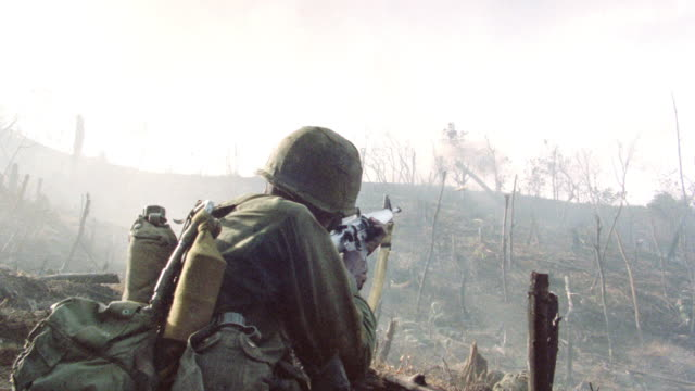 soldiers run toward explosions on a hillside. - vietnamkrieg stock-videos und b-roll-filmmaterial