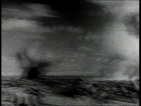vídeos de stock e filmes b-roll de soldiers running across desert / soldiers ducking for cover / shell explosion / soldiers crouching and advancing - 1942