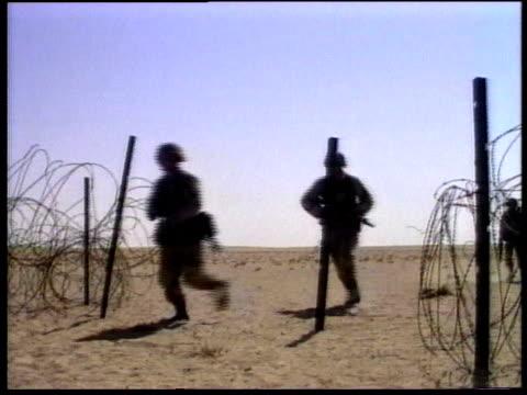 soldiers running in desert past coils of barbed wire / tanks driving in desert - operation desert storm bildbanksvideor och videomaterial från bakom kulisserna