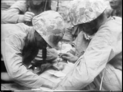 Soldiers running / montage of soldiers using flamethrowers smoking ruins corpses of Japanese soldiers US wounded carried on stretchers attended by...