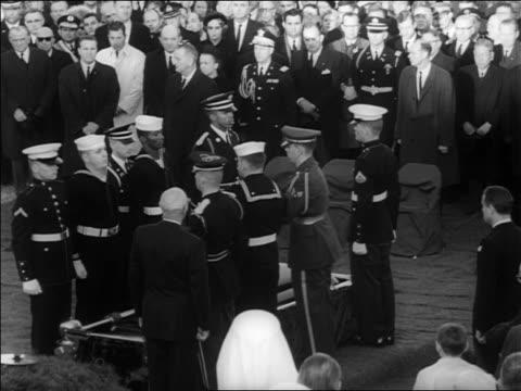 vídeos de stock, filmes e b-roll de b/w 1963 soldiers sailors passing folded flag from jfk's coffin to man saluting / arlington - autoridade