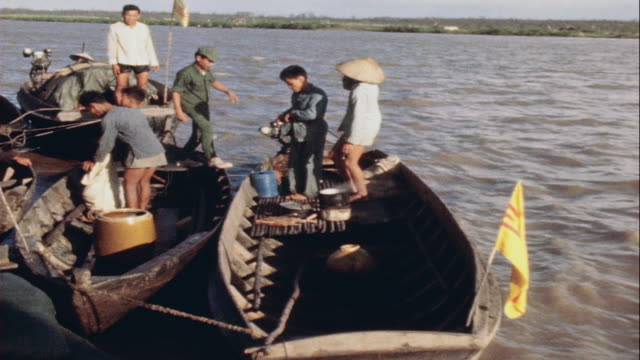 Soldiers searching sampans at mobile river security checkpoint / Vietnam
