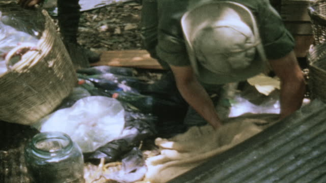 soldiers searching through equipment and supplies found at abandoned viet cong campsite / vietnam - formato panoramico con bande nere video stock e b–roll