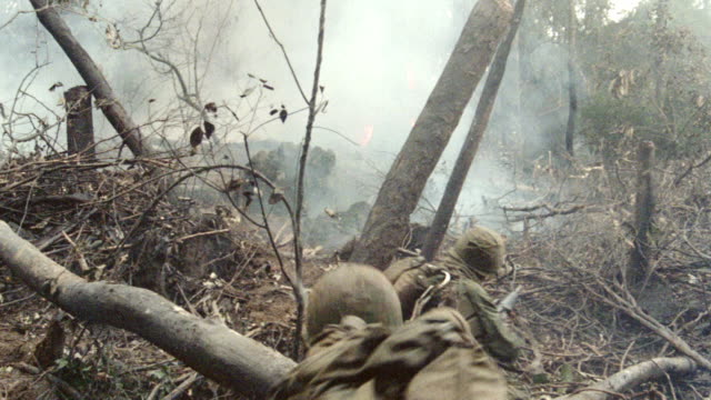 soldiers shoot their weapons into a smokey jungle. - vietnam war stock videos & royalty-free footage