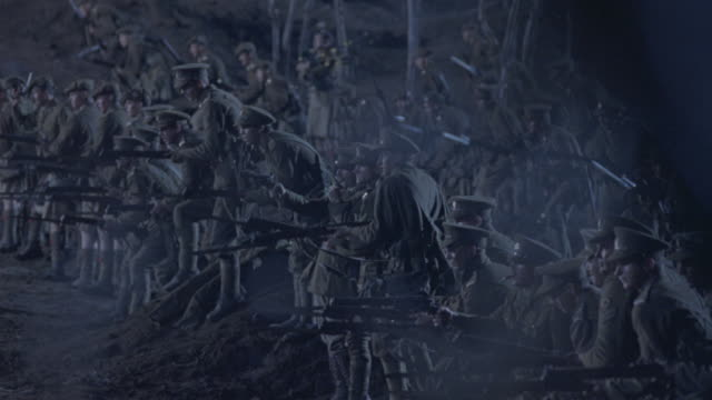 Soldiers shooting guns march forward on a battlefield.