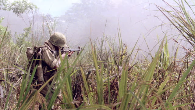 a soldiers shoots his weapon into a smokey jungle. - machine gun stock videos & royalty-free footage