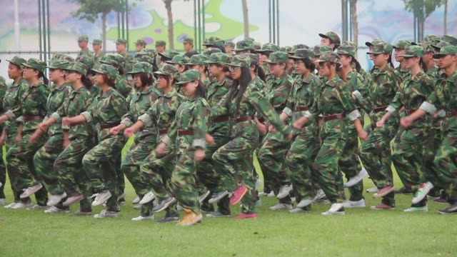 Soldiers shout as they march during military drills at a university.