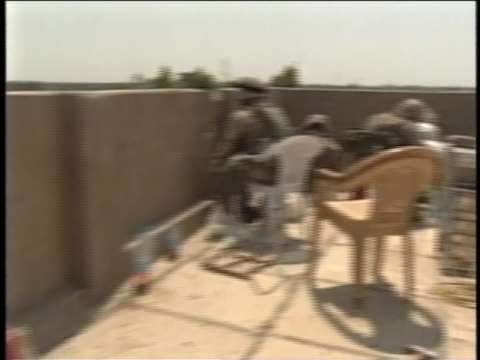 soldiers sit in chairs on a roof as another soldier sights his weapon through a hole in the wall. - al fallujah stock videos & royalty-free footage