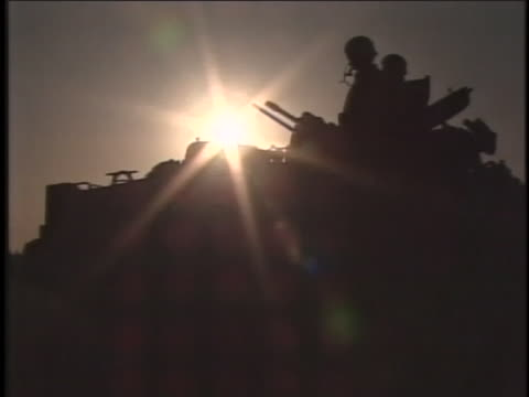 soldiers sit in silhouette atop military vehicle. - al fallujah stock videos & royalty-free footage