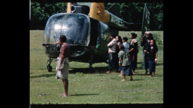 Soldiers sit under trees and drink from coconuts / people in field standing around US Marine Kaman HH43 helicopter From the home movie collection of...