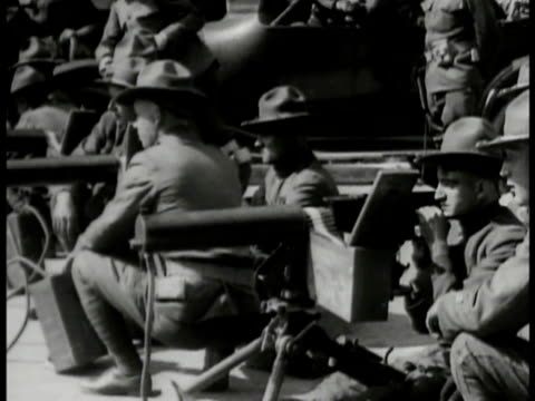 vídeos de stock e filmes b-roll de s soldiers sitting by rows of machine gun turrets w/ ammunition boxes policemen organizing stacks of newspapers handing them out to crowd soldier... - 1919