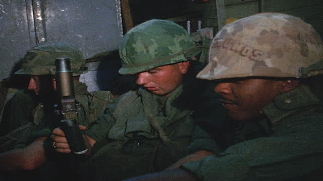 vídeos de stock, filmes e b-roll de soldiers sitting in cargo plane talking and shoulder sleeve insignia and camouflage on helmet / vietnam - formato letterbox