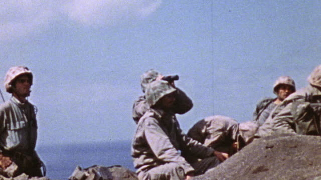 soldiers sitting on a hillside using binoculars and a field telephone while on lookout duty / iwo jima japan - iwo jima island stock videos and b-roll footage