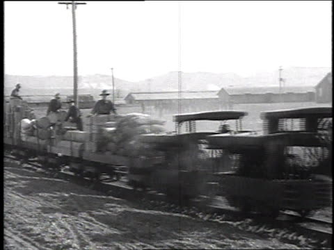 Soldiers sitting on flatbed of small train carrying supplies through camp other units drilling in the background / Camp Sherman Chillicothe Ohio...