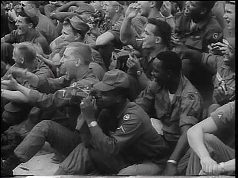 vídeos de stock, filmes e b-roll de b/w 1967 soldiers sitting on ground in audience laughing clapping at uso show / vietnam war - equipamento fotográfico