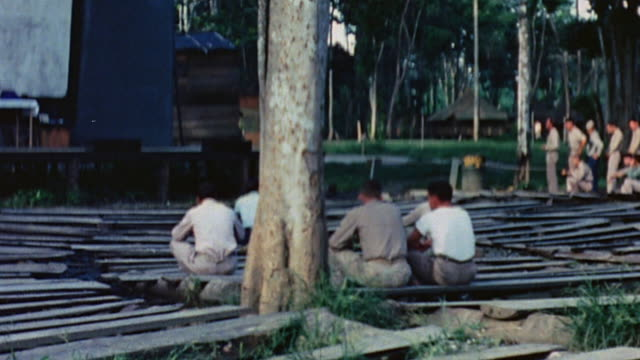 soldiers sitting on makeshift pews, and taking their turn for confession following outdoor church services at camp adams - 懺悔点の映像素材/bロール