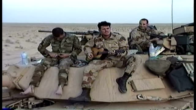 soldiers sitting on tank one playing acoustic guitar - natural land state stock videos & royalty-free footage