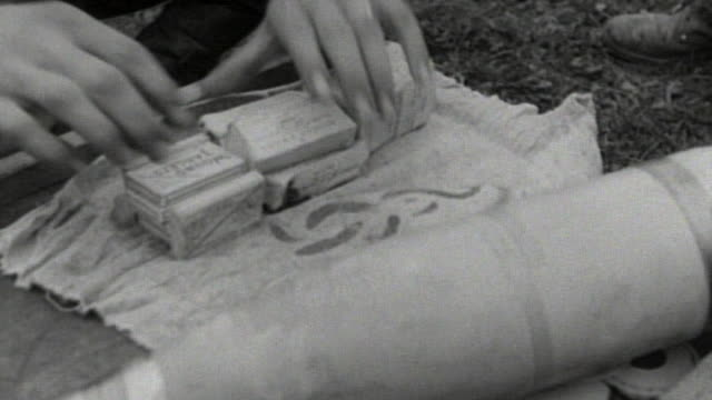 """soldiers stacking and wrapping boxes of """"wound tablets"""" in burlap, stuffing packages into artillery shell casings, and screwing the nose cone down /... - 荒い麻布点の映像素材/bロール"""