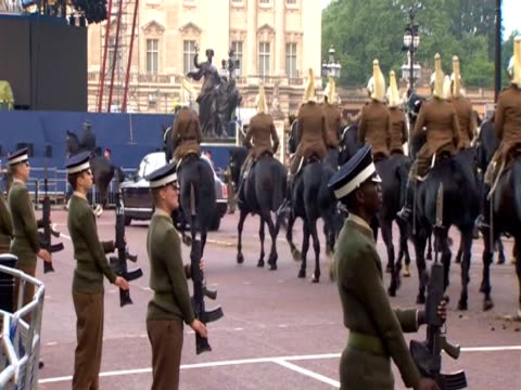 soldiers stand at attention as guards ride by on horseback in a rehearsal for a jubilee procession. - recreational horse riding stock videos & royalty-free footage