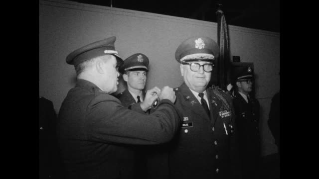 Soldiers stand at attention as officer decorated with new insignia