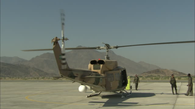 vidéos et rushes de soldiers stand next to an idling helicopter on a military base in saudi arabia. - armée de terre