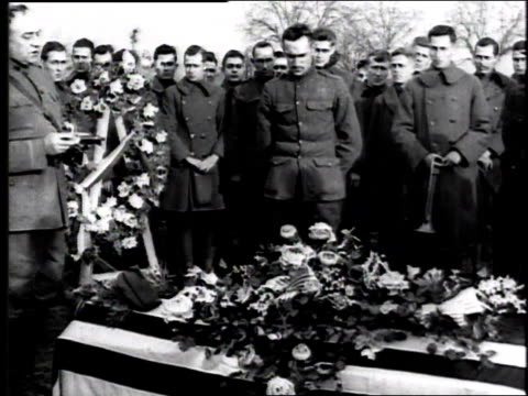 soldiers standing around a coffin at a military funeral while one man speaks and then salutes deceased / france - 1918 stock videos and b-roll footage