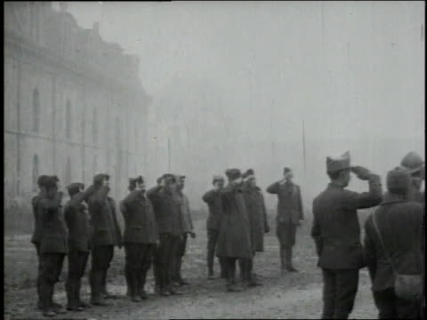 soldiers standing at attention saluting american flag / - armistizio video stock e b–roll