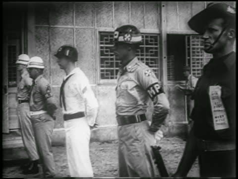 vidéos et rushes de b/w 1953 soldiers standing in line outside of building where korean war armistice is being signed - 1953