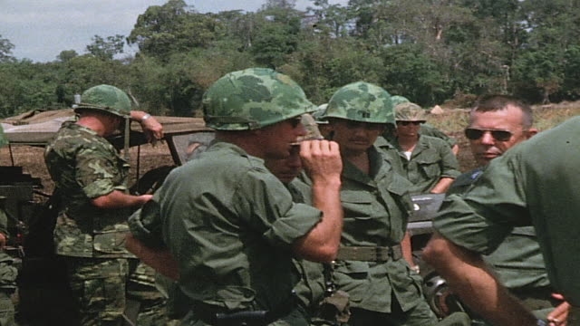 vídeos de stock, filmes e b-roll de soldiers standing in open field and beneath small tent talking and using radio / vietnam - formato letterbox