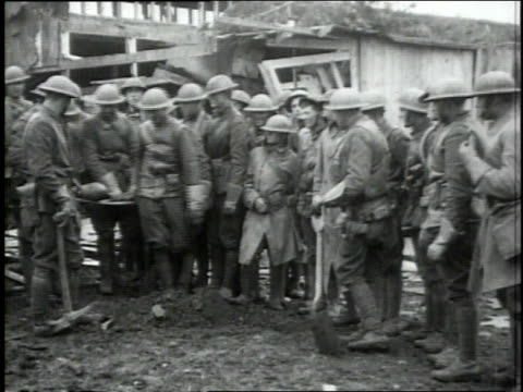 soldiers standing in semicircle watching two soldiers digging a grave / soldiers carry in shell on stretcher they bury it and put up a cross over... - waffenstillstand krieg stock-videos und b-roll-filmmaterial