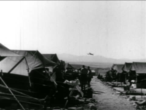 b/w 1956 soldiers standing outside of tents in camp / airplane flies over in background / israel - campo militare video stock e b–roll