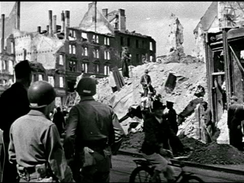 soldiers standing talking in street w/ people on rubble mound bg vs male in coat hat walking in around rubble of heavily bombed buildings possibly... - postwar stock videos and b-roll footage