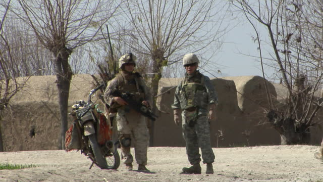 stockvideo's en b-roll-footage met ws soldiers standing with tents in background / mausa qala helmand province afghanistan - vertaling