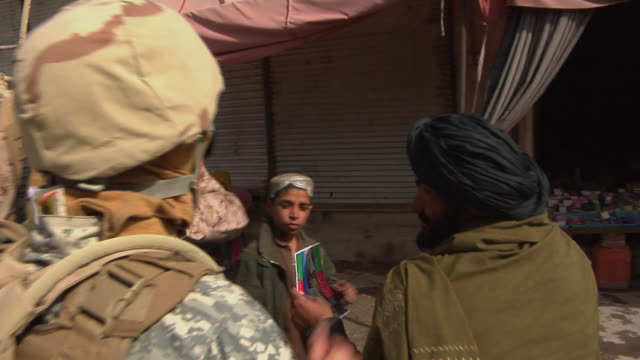 soldiers talking to civilians / musa qala helmand province afghanistan - 言語翻訳点の映像素材/bロール