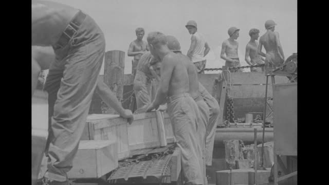 soldiers unload supplies as they arrive in guadalcanal / crane moves stack of material / vs shirtless soldiers place wooden crates on flatbed trailer... - mp stock-videos und b-roll-filmmaterial