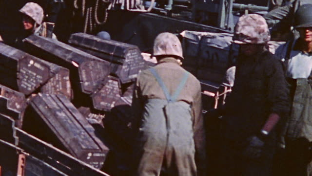 vídeos de stock, filmes e b-roll de soldiers unloading shells onto the beach and halftracked loaded truck driving off lst during world war ii - carro blindado