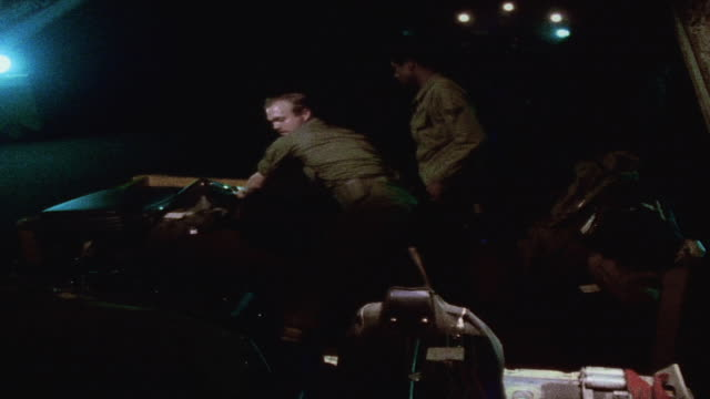 soldiers unloading suitcases and personal gear on airport tarmac at night / da nang vietnam - ダナン点の映像素材/bロール