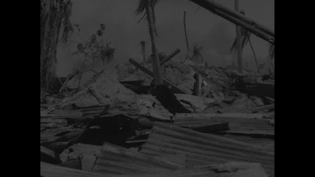 soldiers use bullhorn to call japanese out of nearly destroyed bunker / vs japanese soldiers cross over rubble most clad only in underpants / vs... - 装甲車点の映像素材/bロール