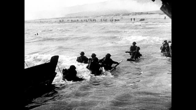 soldiers wade ashore in france / landing at omaha beach / wet soldiers pull dingy ashore / american soldier narrates the scene dday landing on omaha... - normandie stock-videos und b-roll-filmmaterial
