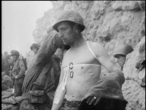 soldiers wading toward beach pulling inflatable boat / men helping wounded soldier onto beach / soldier standing on beach / soldiers standing on... - d day stock videos & royalty-free footage