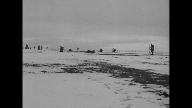 VS US soldiers wait for military action on a snowy field in Belgium one holds a bazooka others stand nearby some kneel or are in foxholes / Note...