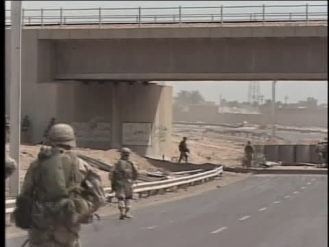 soldiers wait under an overpass, as war other soldiers approach. - al fallujah stock videos & royalty-free footage