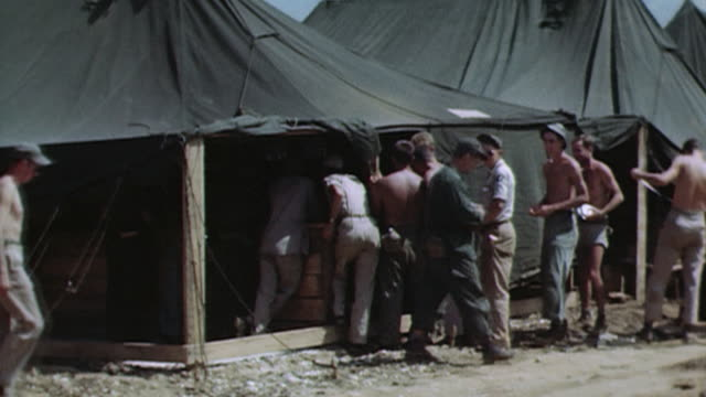 pan soldiers waiting in line at a chaplain's tent at a military camp / okinawa ryukyu islands japan - pazifikkrieg stock-videos und b-roll-filmmaterial