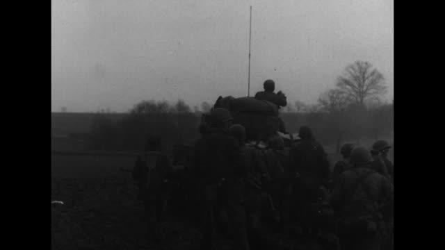 soldiers walk behind tank across field / german prisoners of war cross field / line of soldiers follow tanks / tank fires across rhine river /... - kampfpanzer stock-videos und b-roll-filmmaterial