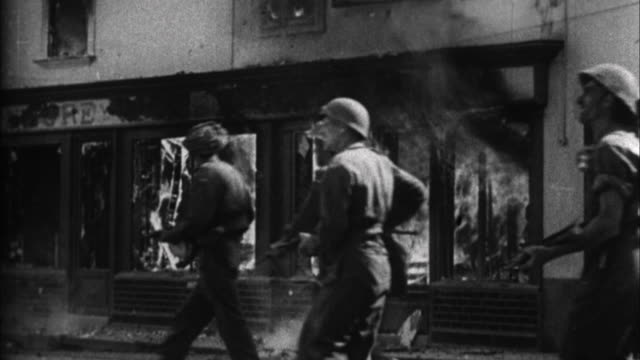 soldiers walk past burning buildings / france - battle stock videos & royalty-free footage