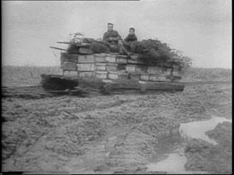 Soldiers walk through mud in UKraine / tanks roll through water and mud / map of Germany and Russia / Russian guns fire / explosions surround tanks /...